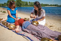 Beautiful female receiving energy sound massage with singing bowls and body massage on a river bank Royalty Free Stock Photo