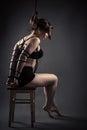 Beautiful female slave sitting bondage ropes on chair Royalty Free Stock Photo