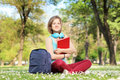 Beautiful female student with book and headphones sitting on a g grass in park Royalty Free Stock Photography