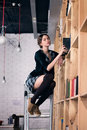 Beautiful female student in a library on stairs puts books the Stock Photos