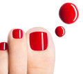 Beautiful female toes with red pedicure and drops of nail polish over white background Stock Photos