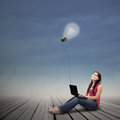 Beautiful female using laptop under lit bulb outdoor student looking at with Royalty Free Stock Photo