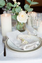 Beautiful festive table setting with flowers candles white cloth and napkins close up Royalty Free Stock Images