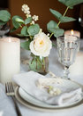 Beautiful festive table setting with flowers candles white cloth and napkins close up Stock Photography