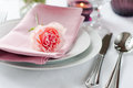 Beautiful festive table setting with roses candles shiny new cutlery and napkins on a white tablecloth Stock Photo