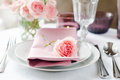 Beautiful festive table setting with roses candles shiny new cutlery and napkins on a white tablecloth Royalty Free Stock Photography