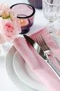 Beautiful festive table setting with roses candles shiny new cutlery and napkins on a white tablecloth Stock Images