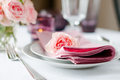 Beautiful festive table setting with roses candles shiny new cutlery and napkins on a white tablecloth Royalty Free Stock Images
