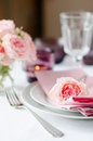 Beautiful festive table setting with roses candles shiny new cutlery and napkins on a white tablecloth Royalty Free Stock Image