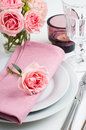 Beautiful festive table setting with roses candles shiny new cutlery and napkins on a white tablecloth Royalty Free Stock Photos
