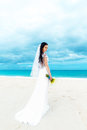 Beautiful fiancee in white wedding dress with big long white tra train and bouquet stand on shore sea Royalty Free Stock Image