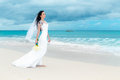 Beautiful fiancee in white wedding dress with big long white tra train and bouquet stand on shore sea Royalty Free Stock Photos