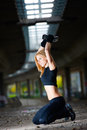 Beautiful fit woman lifting weights outdoors Stock Photo