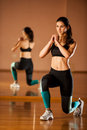 Beautiful fit woman works out in a fitness gym making lunge step Royalty Free Stock Photo