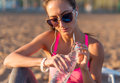 Beautiful fitness athlete woman drinking water after work out exercising on sunset evening summer in beach outdoor Royalty Free Stock Photo