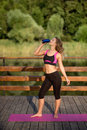 Beautiful fitness athlete woman drinking water after workout exercising on sunset evening Royalty Free Stock Photo