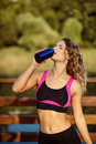 Beautiful fitness athlete woman drinking water after workout exercising on sunset evening summer outdoor