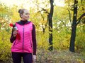 Beautiful fitness sport girl in sportswear with sports water bottle or isotonic drink in hand in autumn forest. Royalty Free Stock Photo