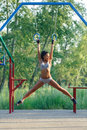 Beautiful fitness woman fitness workout on gymnastic rings sunny outdoor sporty girl doing sit ups outdoor Royalty Free Stock Images