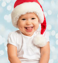 Beautiful funny baby in a christmas hat on blue background Royalty Free Stock Images