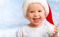 Beautiful funny baby in a christmas hat on blue background Stock Images