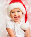 Beautiful funny baby in a christmas hat on pink background Royalty Free Stock Photos