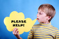Beautiful funny blond boy holding a message please help child yellow cloud saying Royalty Free Stock Photo