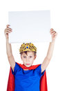 Beautiful funny child dressed as king with a crown holds a rectangular white blanc board space for text Stock Photos