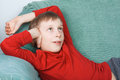 Beautiful funny child wearing bright red sweater resting on a sofa dreaming smiling and Stock Photography