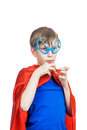 Beautiful funny child wearing funny glasses pretending to be superman looking shy superhero concept Royalty Free Stock Photography
