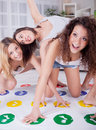 Beautiful funny girls play twister in the room three young Royalty Free Stock Image