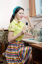 Beautiful funny young pinup woman with sewing machine pretty and cup of tea Stock Photo