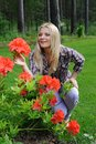 Beautiful gardener woman with red flower bush Stock Images