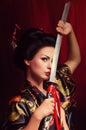 Beautiful geisha in kimono with samurai sword Stock Photos