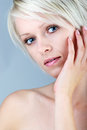 Beautiful gentle woman with a wistful look young blond innocent posing her hand to her cheek bare head and shoulders portrait Stock Images