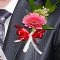 Beautiful gerbera boutonniere on groom suit and rose or tuxedo Stock Photo