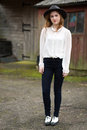 Beautiful ginger teenager in front of stables portrait a teenage girl wearing a hat white shirt with a pearl collar black trousers Royalty Free Stock Photography