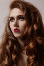 Beautiful ginger young woman with luxury hair style and fashion gloss makeup. Beauty closeup model with red hair