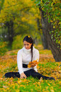 Beautiful girl in the autumn forest sitting and gathering leaves Stock Photos