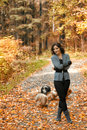 Beautiful girl in the autumn park gray together with her lapdogs Royalty Free Stock Images