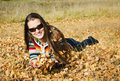 The beautiful girl on autumn walk smiling young woman in dark sun glasses lies yellow leaves Stock Photo
