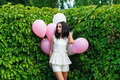 Beautiful girl with balloons in green hedgerow outdoors Stock Photo