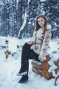 Beautiful girl in a beige short coat with flowing hair is sitting on a wooden frame