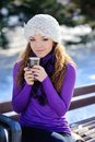 Beautiful girl on a bench with a cup of coffee in the winter Royalty Free Stock Photos