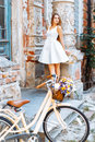 Beautiful girl with a bicycle near an old blue door Royalty Free Stock Photo