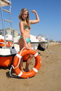 Beautiful girl in bikini with lifebuoy shows power soft focus Stock Images