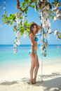 Beautiful girl in bikini posing on the tropical beach under coral tree summer vacation Royalty Free Stock Photography