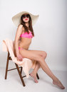 Beautiful girl in bikini, sunglasses and a big hat sitting on a deck chair, holding his hand with a glass of cocktail Royalty Free Stock Photo