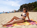 Beautiful girl in bikini tanning on the beach the summer Royalty Free Stock Images