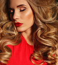 Beautiful girl with blond curly hair and bright evening makeup, wears elegant dress Royalty Free Stock Photo